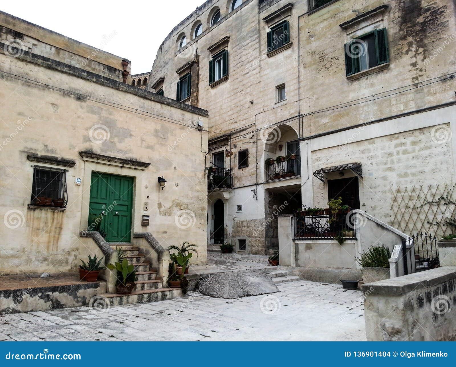 Edificios antiguos con los obturadores verdes y puertas a la ciudad de Matera