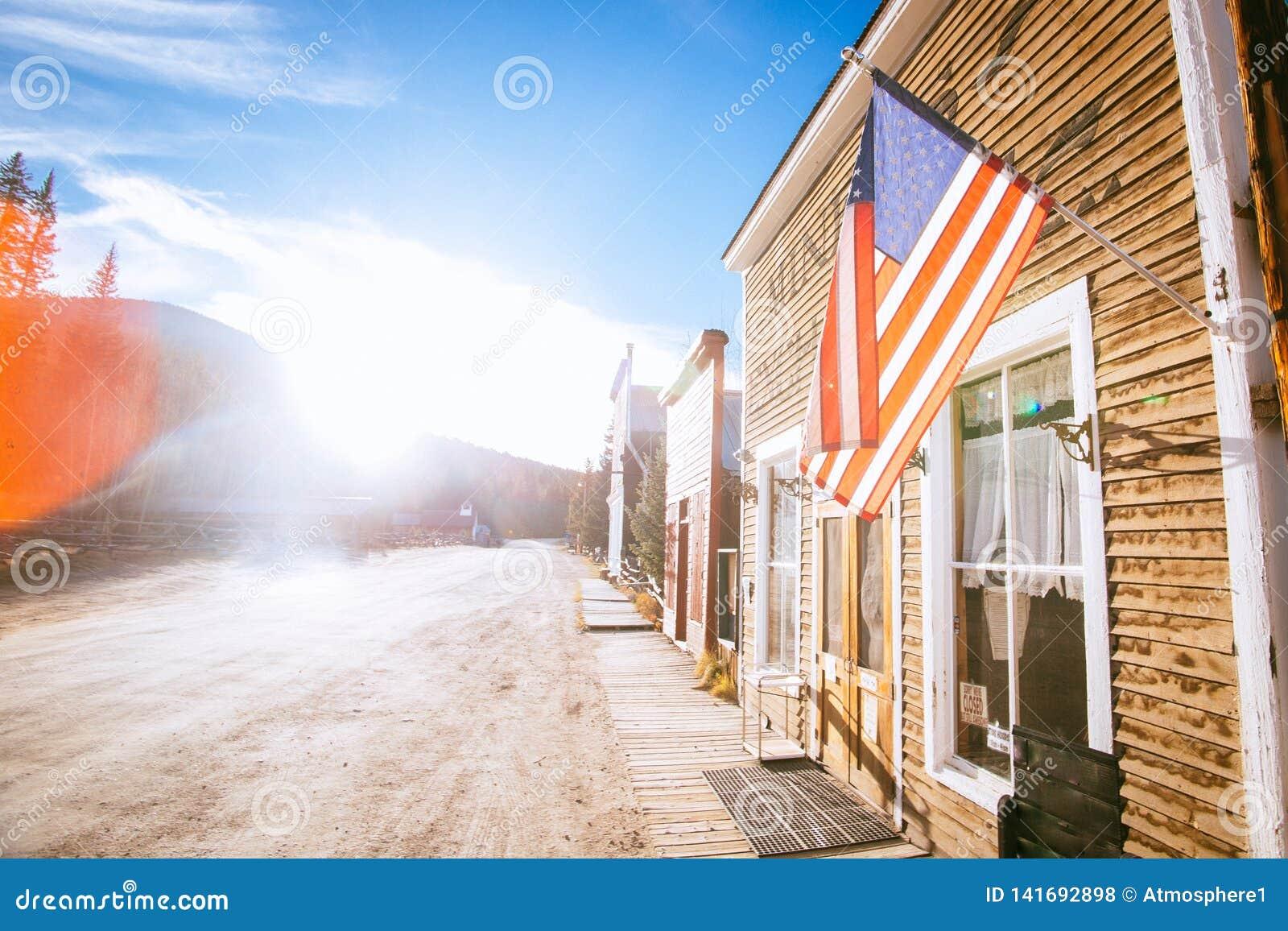 Edificios de madera occidentales viejos con la bandera de los Estados Unidos, en St Elmo Gold Mine Ghost Town en Colorado, los E.