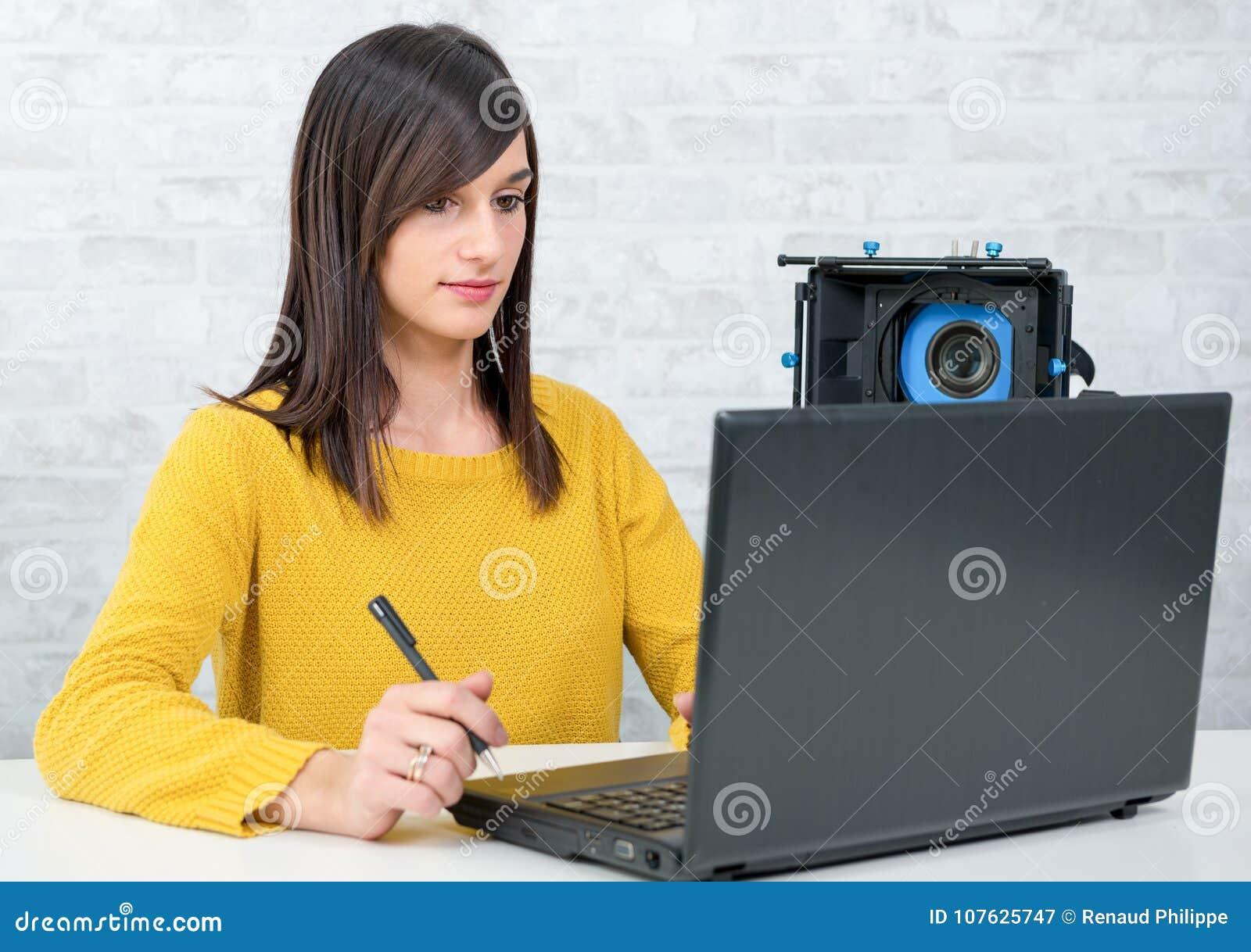 Editor de vídeo de la mujer joven que trabaja en estudio