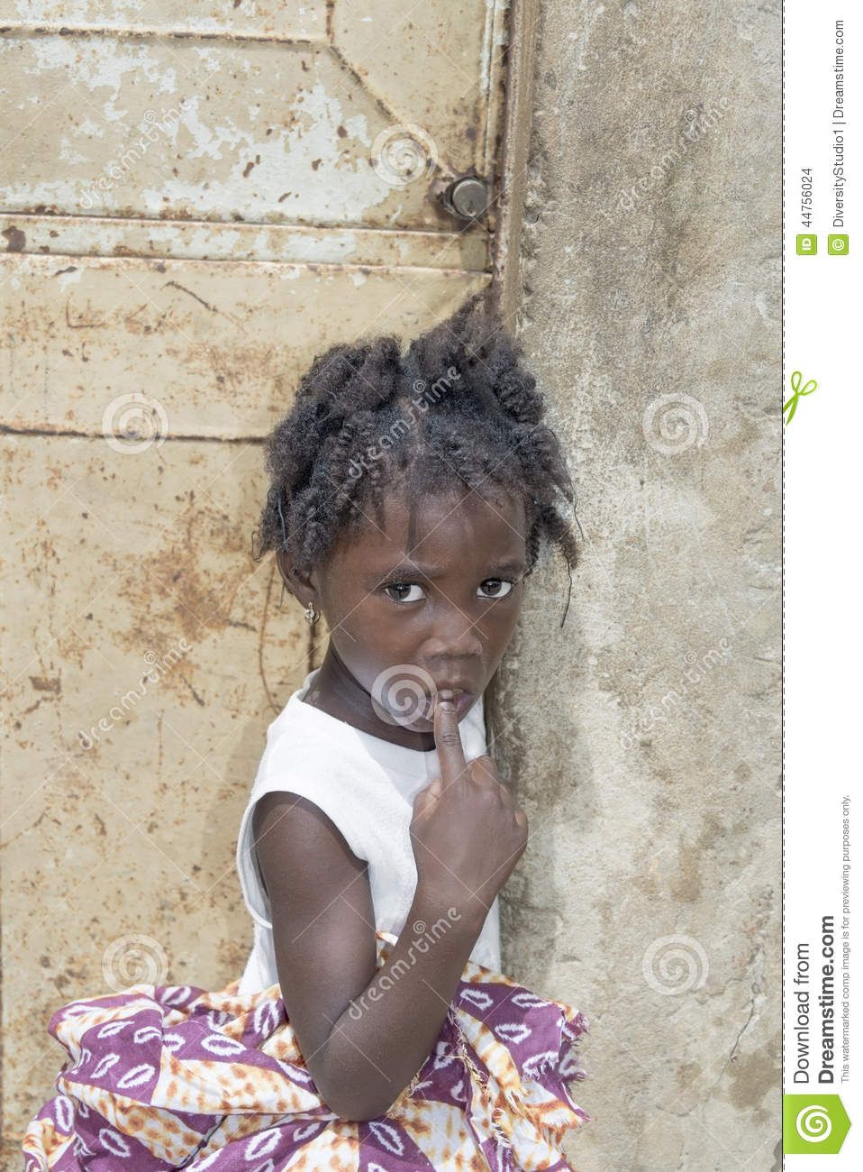 Editorial caption: THIAROYE, SENEGAL, AFRICA – JULY 26, 2014 – Unidentified Senegalese girl in front of a house door