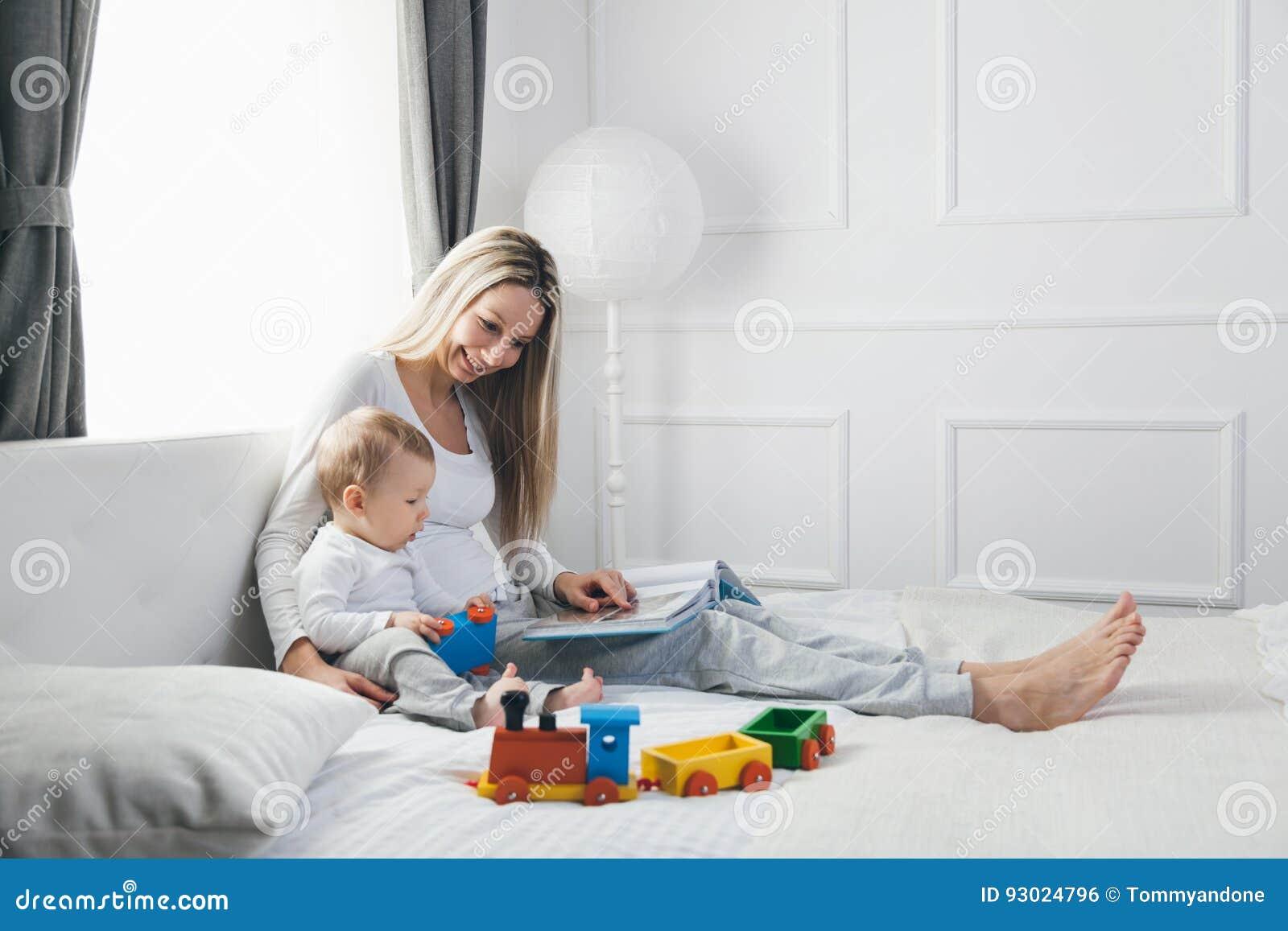 Educação da criança Mãe feliz com sua criança que senta-se na cama e que lê um livro