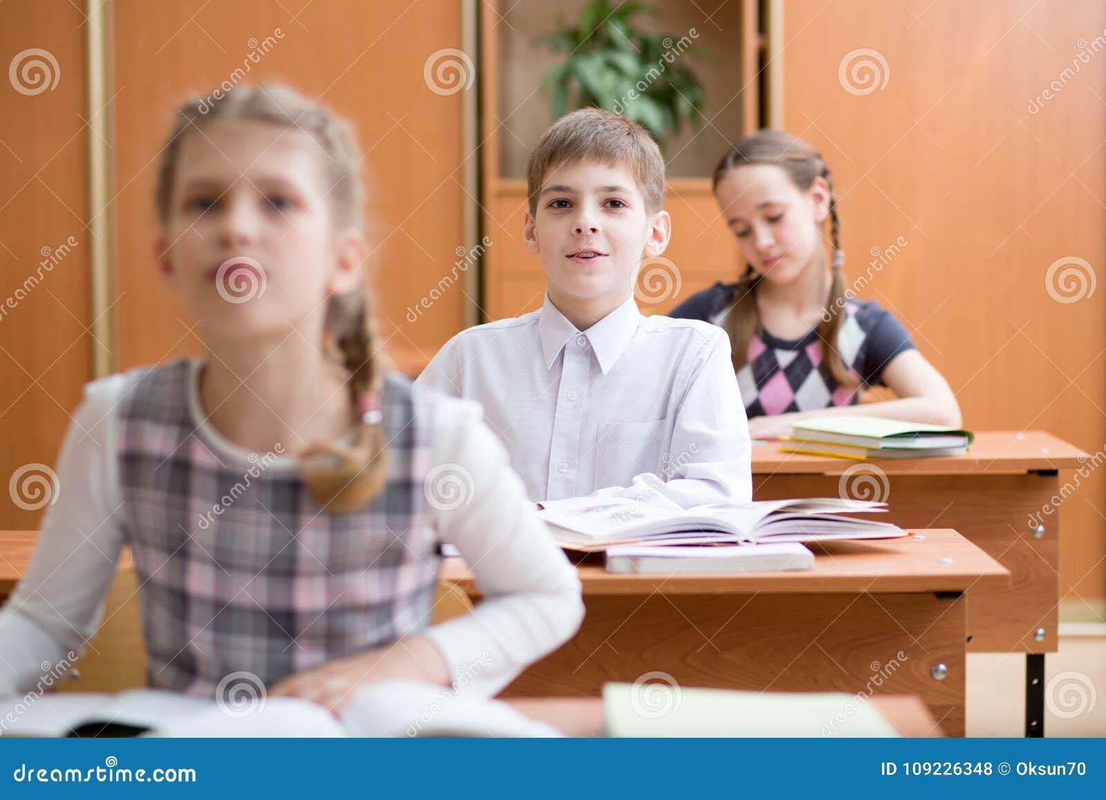 Educação, escola primária, aprendizagem e conceito dos povos - o grupo de escola caçoa o teste da escrita na sala de aula
