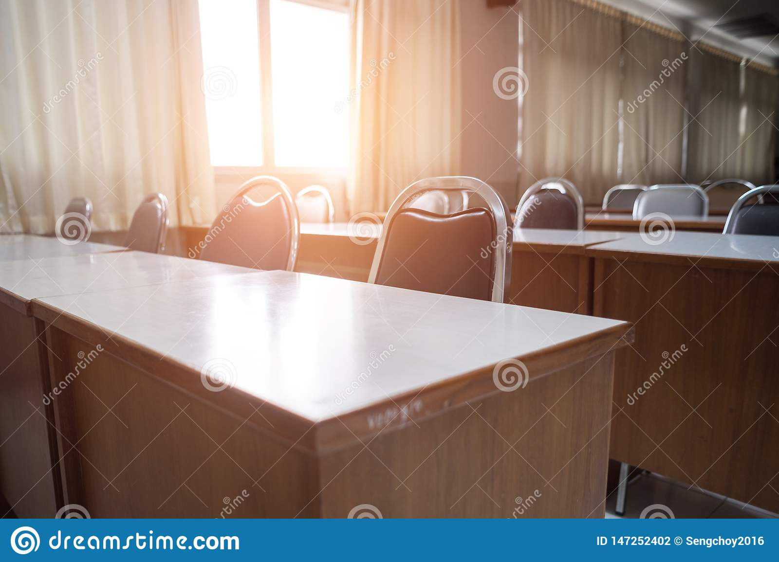 Education concept: Empty college or university classroom with wooden tables and chairs in row without student or teacher in the ro