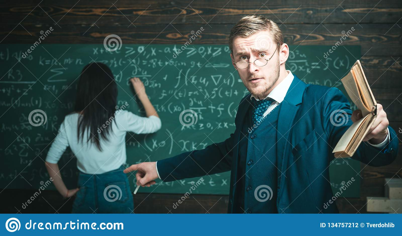 Education concept. Education of surprised teacher man point finger at woman student doing sums on chalkboard
