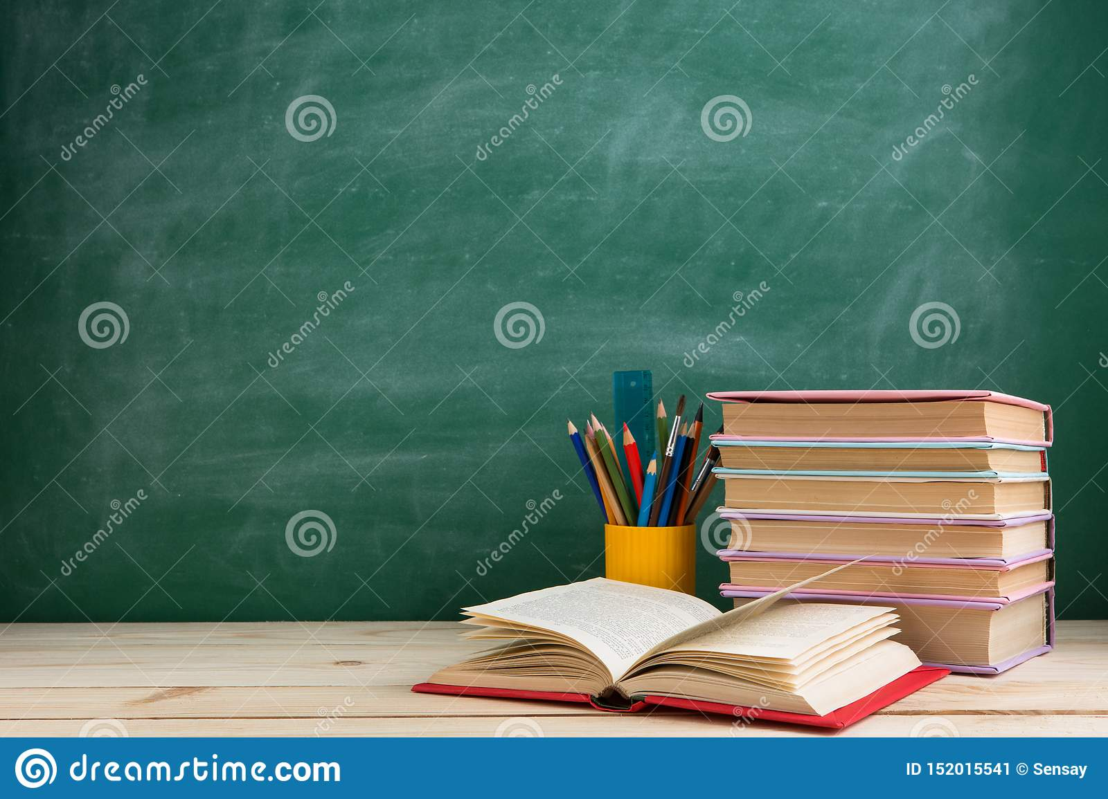 Education and reading concept - group of colorful books on the wooden table in the classroom, blackboard background