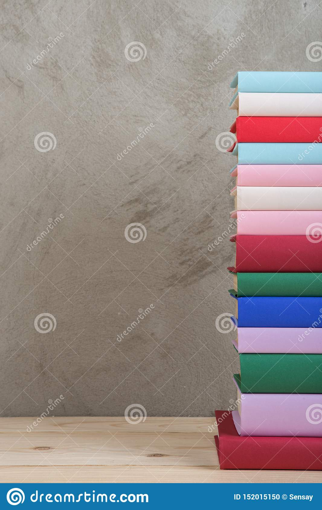 Education and reading concept - group of colorful books on the wooden table, concrete wall blackboard