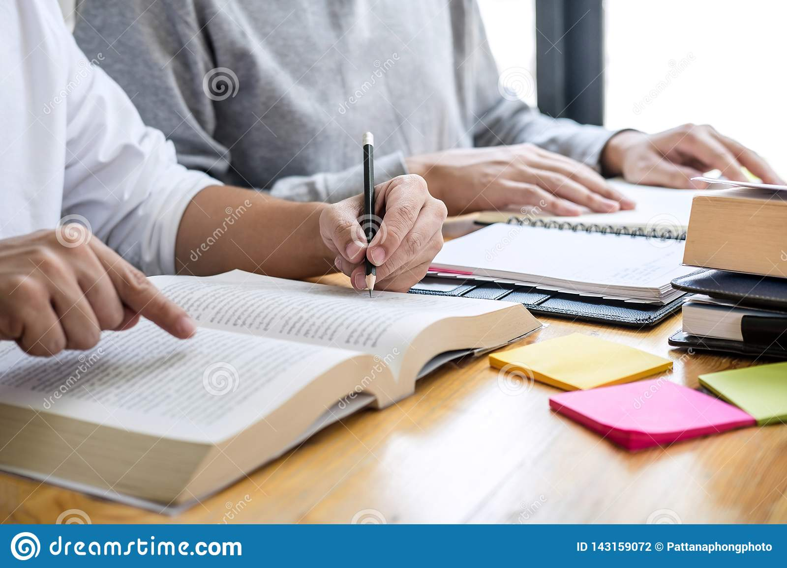 Education, teaching, learning concept. High school students or classmates group tutor in library studying and reading with helps