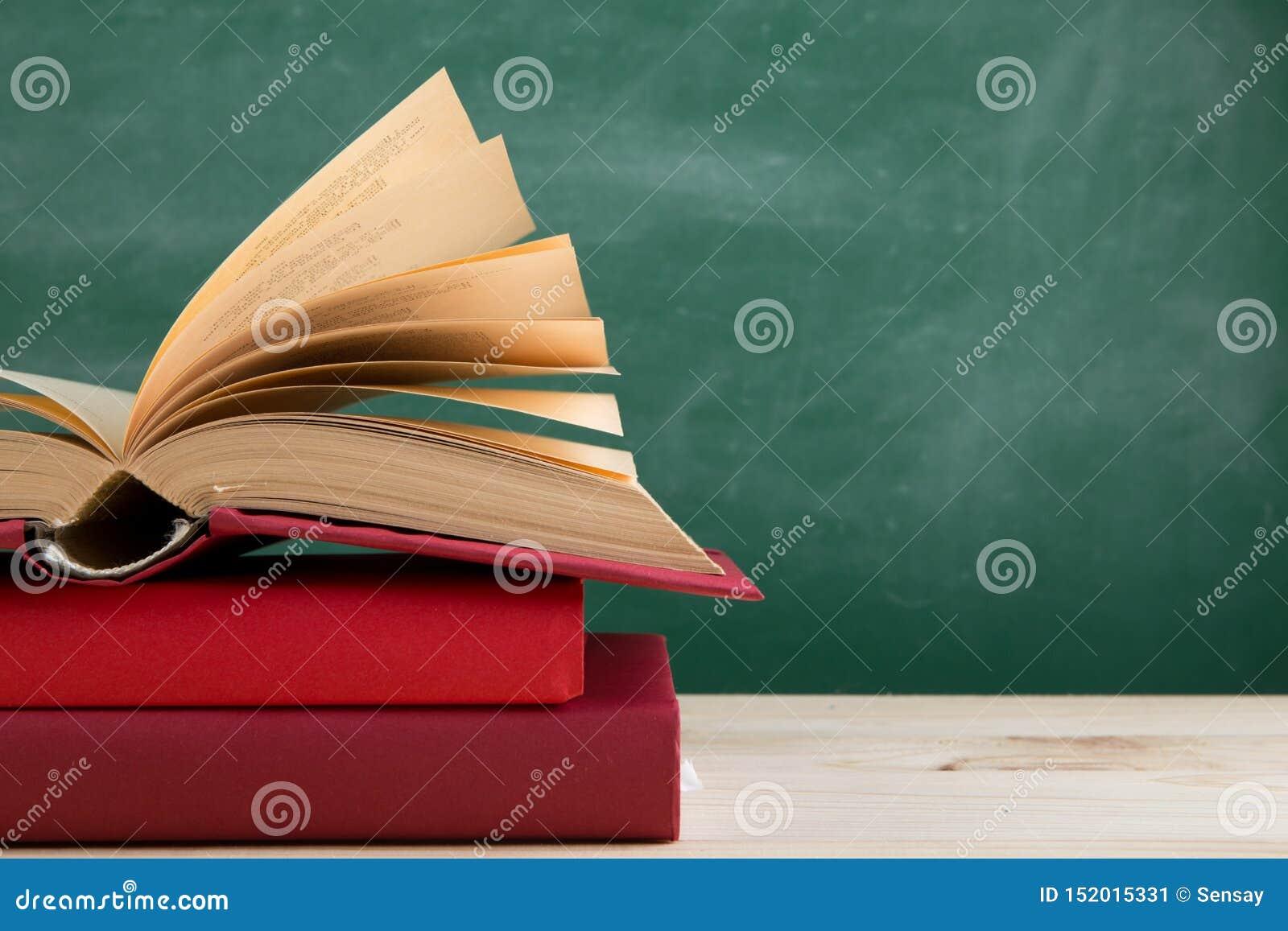Edukacji i czytania pojęcie - grupa kolorowe książki na drewnianym stole w sali lekcyjnej, blackboard tło
