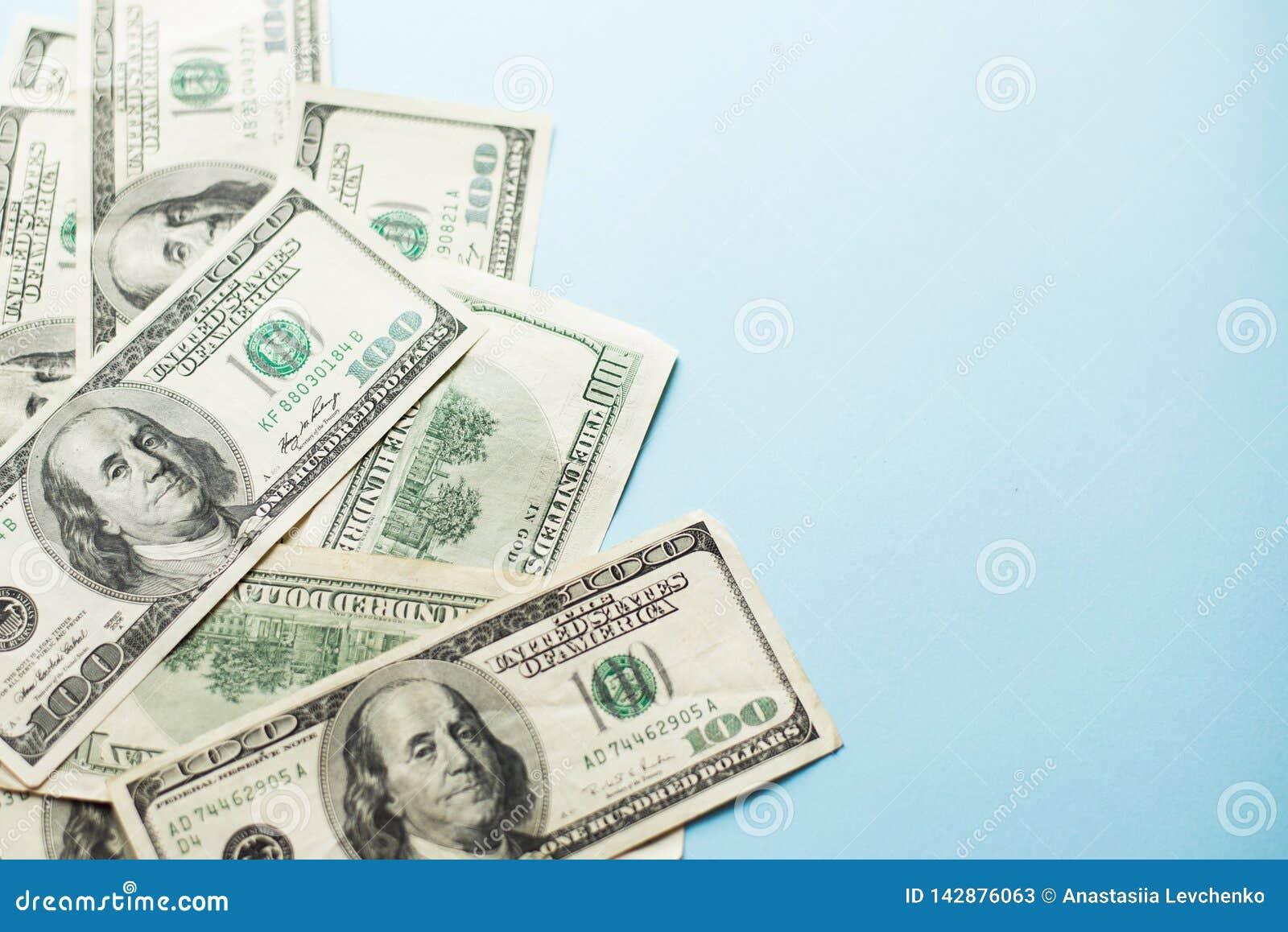 Een aantal honderd Amerikaanse dollarsnota s over lichtblauwe achtergrond Concept