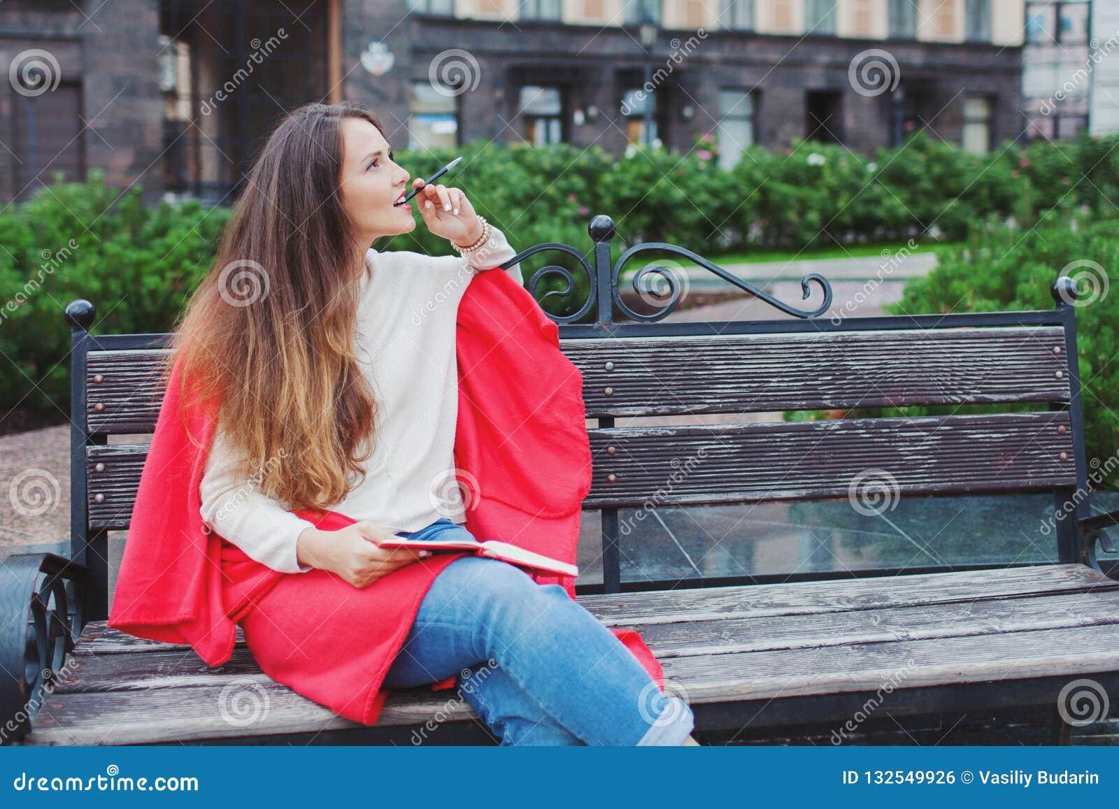 Een aantrekkelijk meisje met lang bruin haar zit op een bank, verbergend achter een rode deken, knagend aan een pen en denkend op
