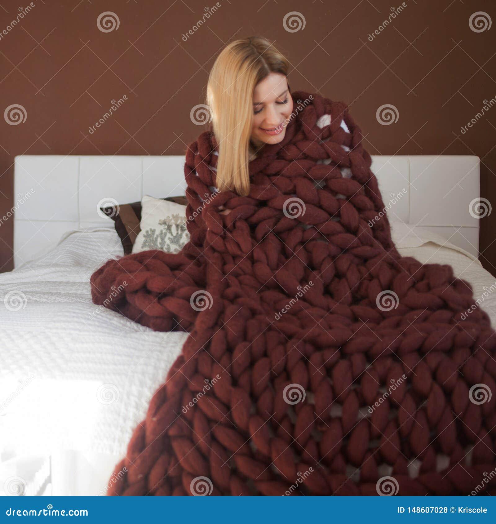 Een aantrekkelijke jonge vrouw is verpakt in een zachte pluizige deken