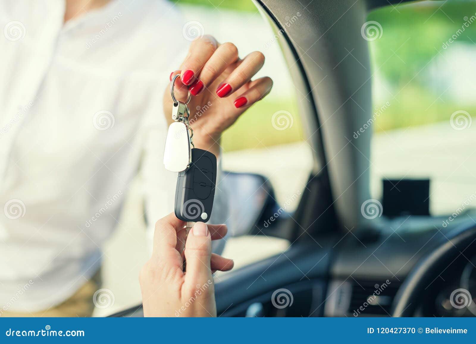 Een aantrekkelijke vrouw in een auto krijgt de autosleutels Huur of aankoop van auto