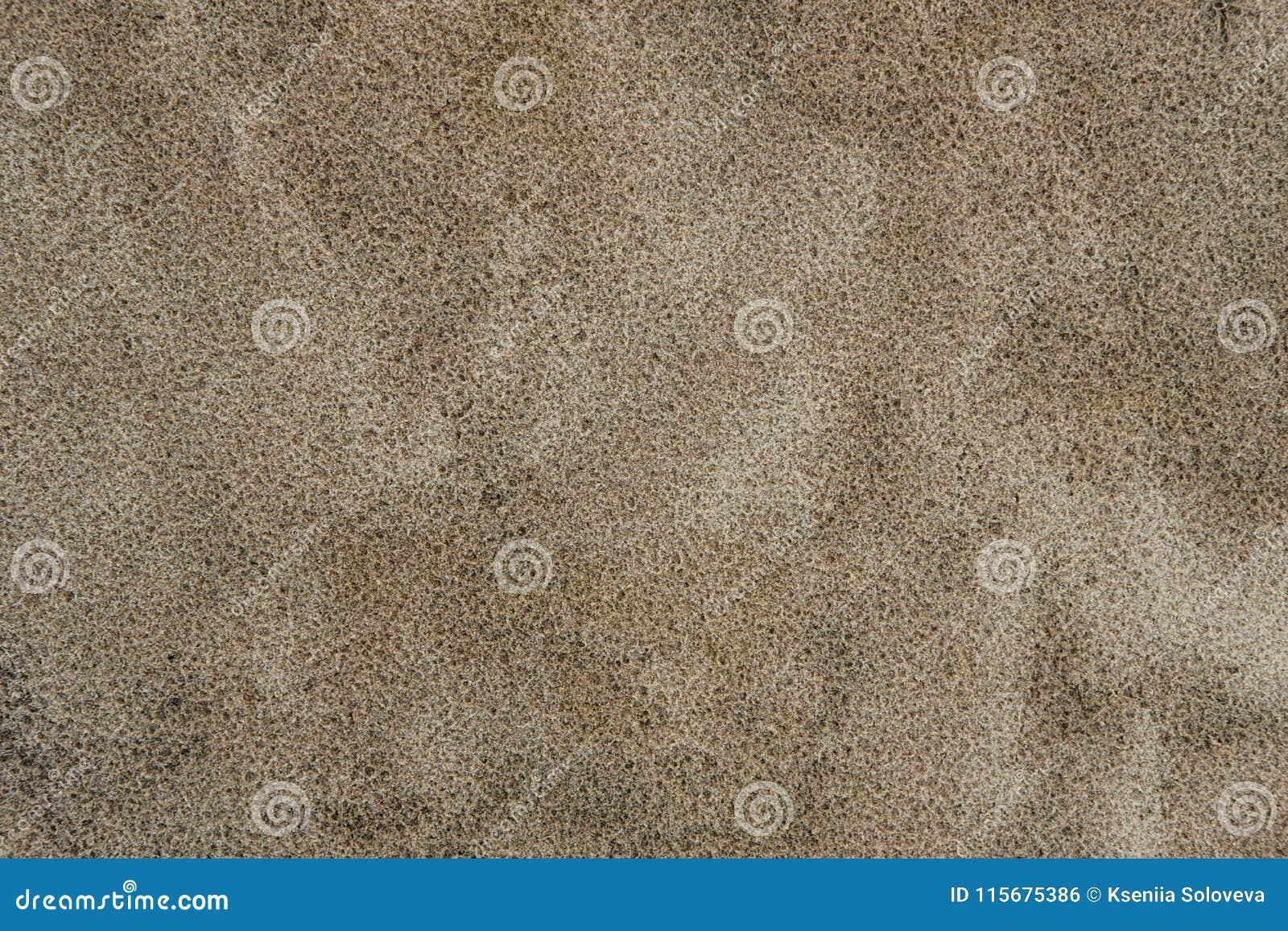 Een achtergrondtextuur van ongeraffineerd, vochtig en korrelig natuurlijk gouden zand