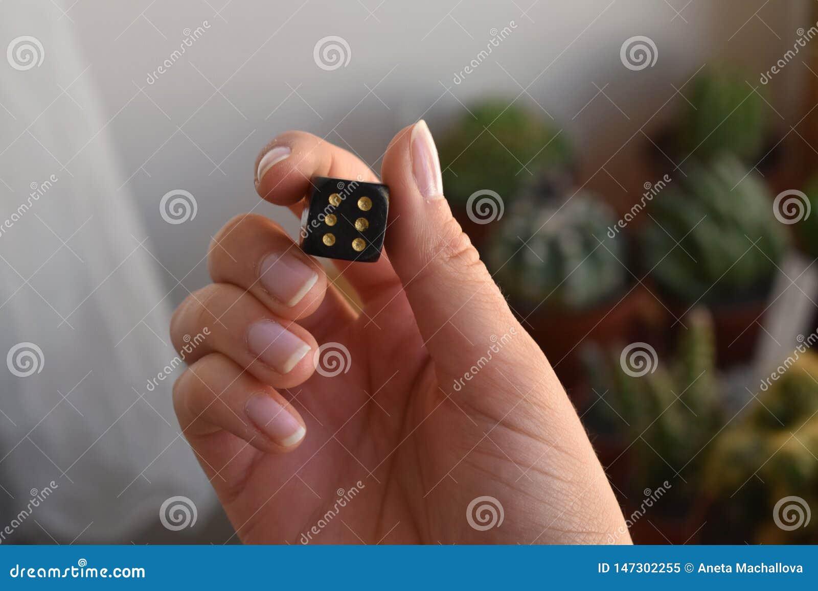 Een anonieme vrouw die een zwarte kubus met gouden punten houden