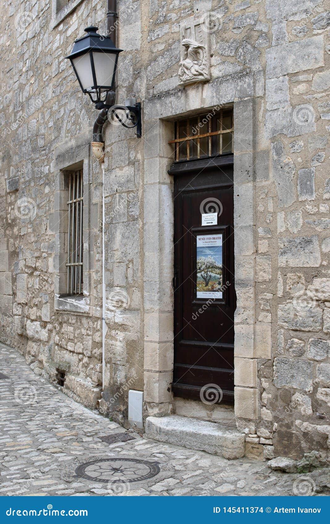 Een antieke houten deur, een ijzerlantaarn en een beeldhouwwerk Pietà boven de deur