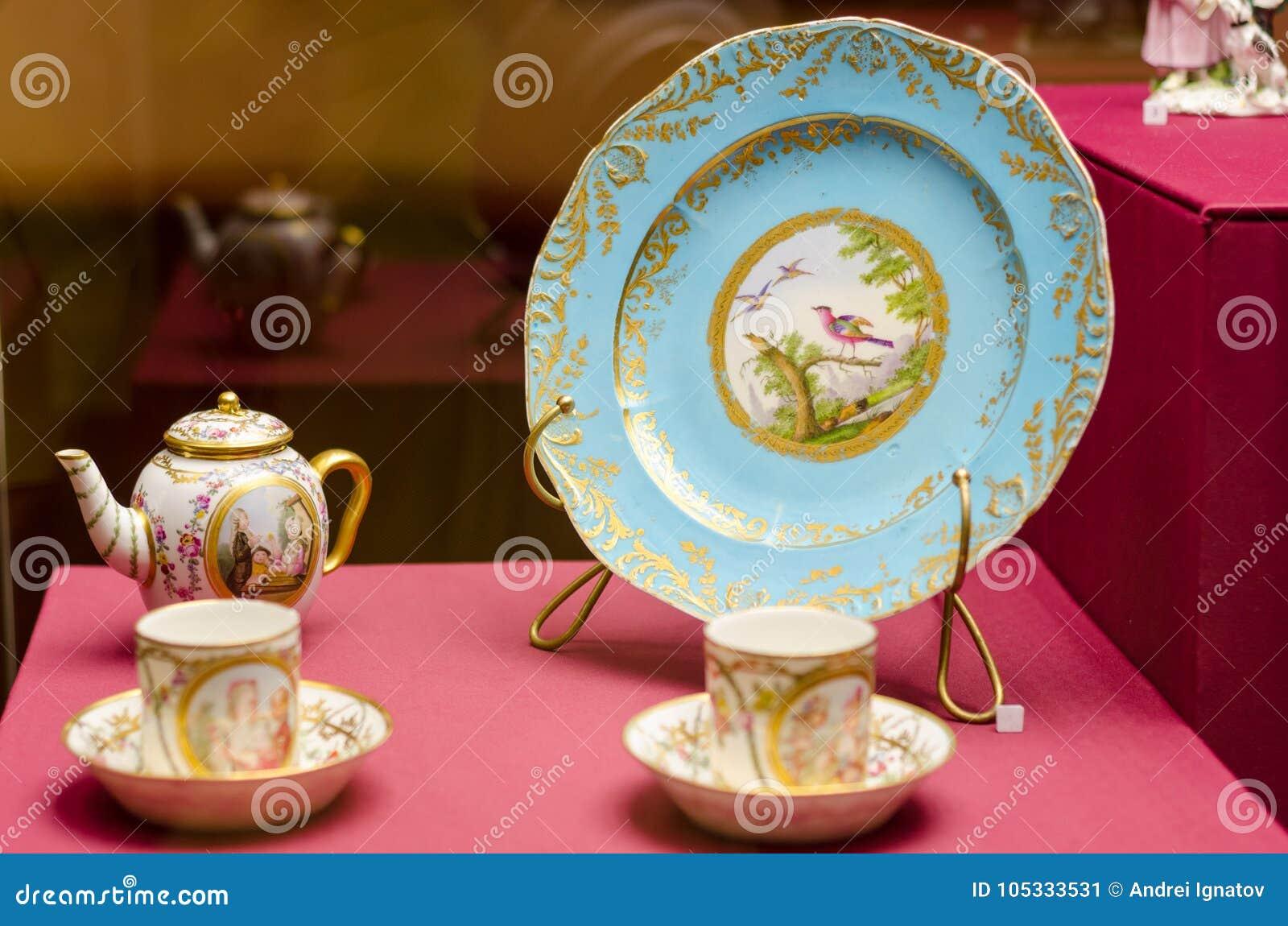 Een antieke reeks ceramische theepotten, koppen, schotels op een houten lijst