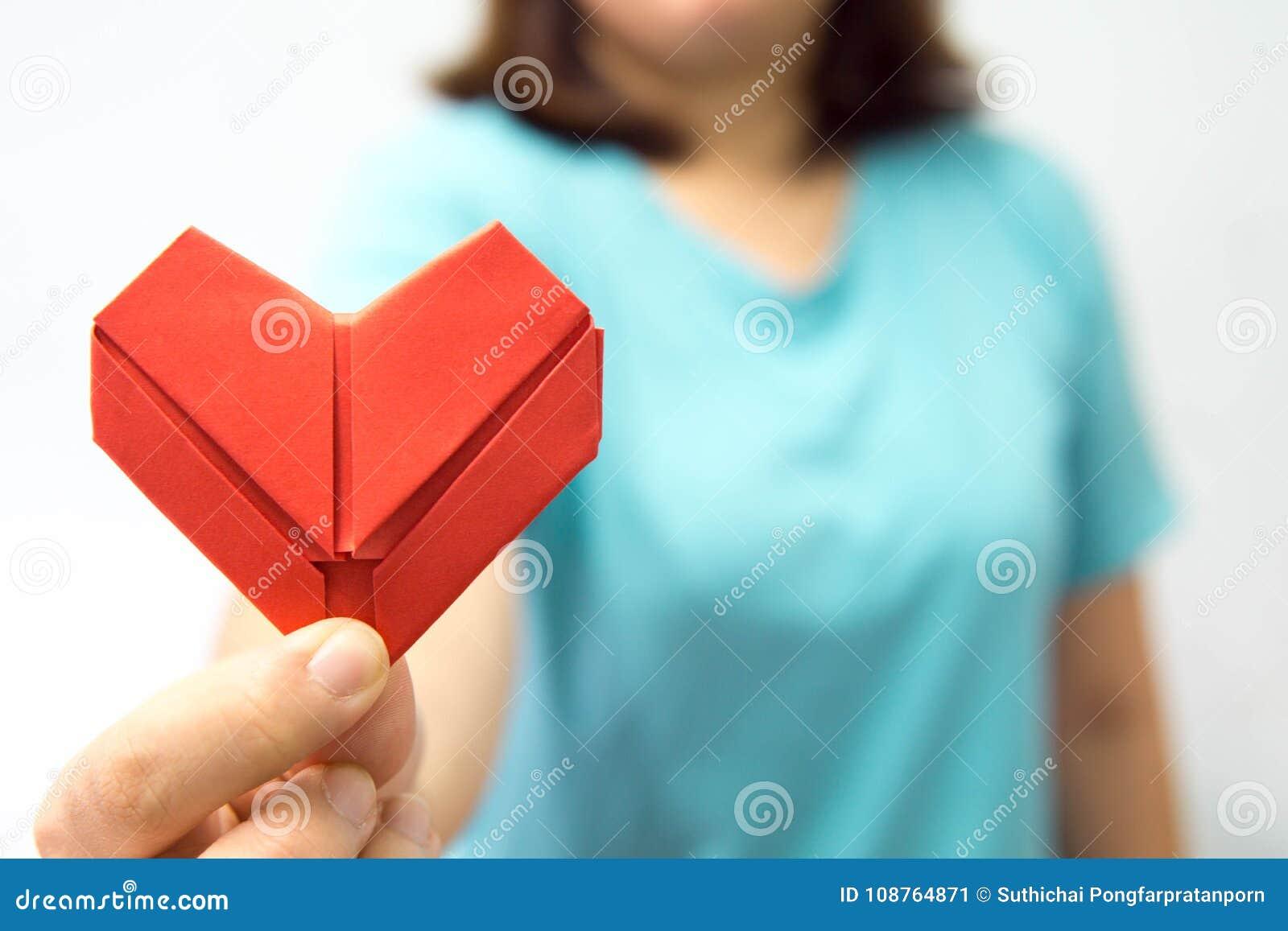 Een Aziatische hartorigami van de vrouwenholding voor haar borsta vrouw die rood hartdocument geven aan iemand De liefde en geeft