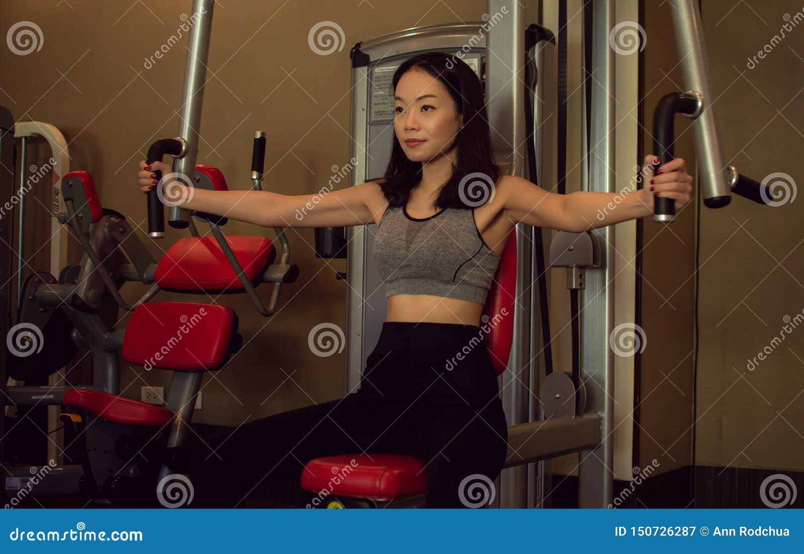 Een Aziatische mooie vrouw leidt in de gymnastiek op