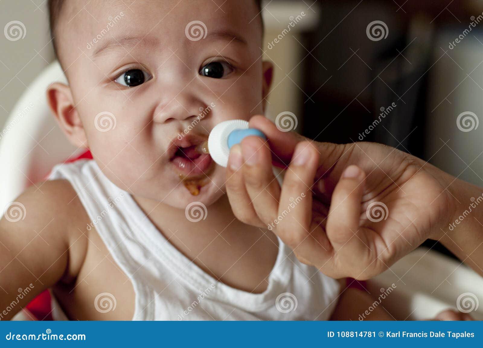 Een babyjongen drinkt zijn vitaminen gebruikend een druppelbuisje