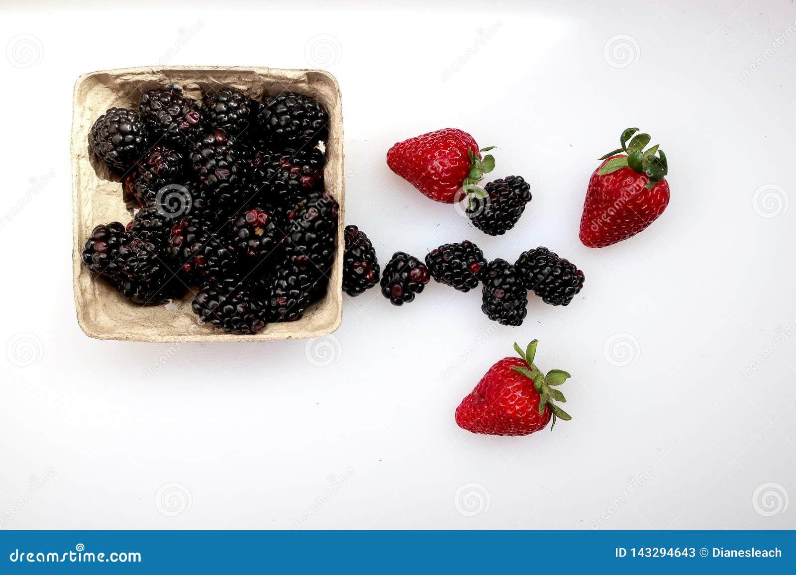 Een bakje van braambessen en drie verse aardbeien op een witte achtergrond