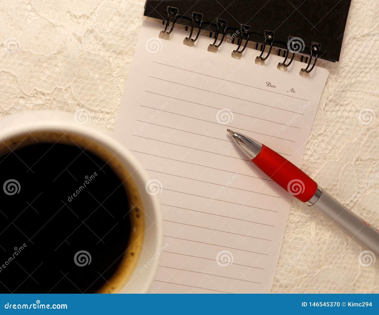 Een ballpoint ligt op een lege gevoerde pagina van een spiraalvormig notitieboekje