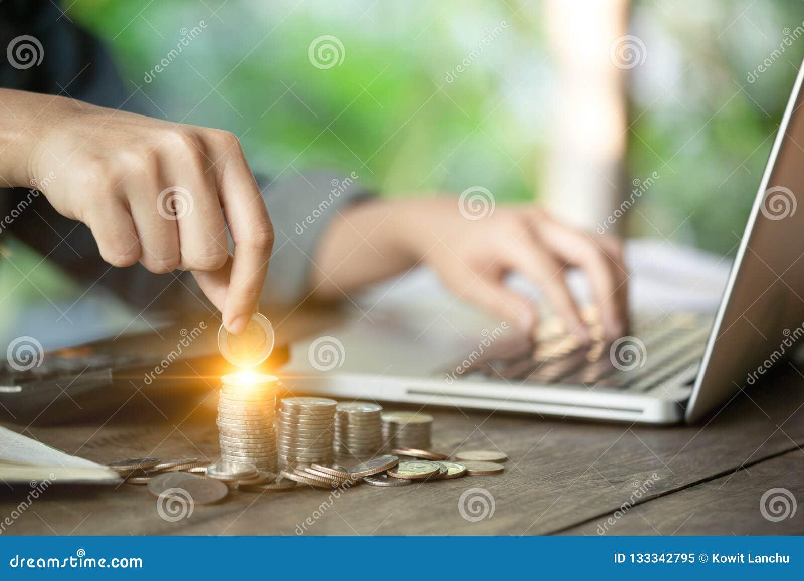 Een bedrijfsvrouwenhand houdt een muntstuk voor het bewaren van geldconcept, en het werken met haar computerlaptop Beheer aan inv