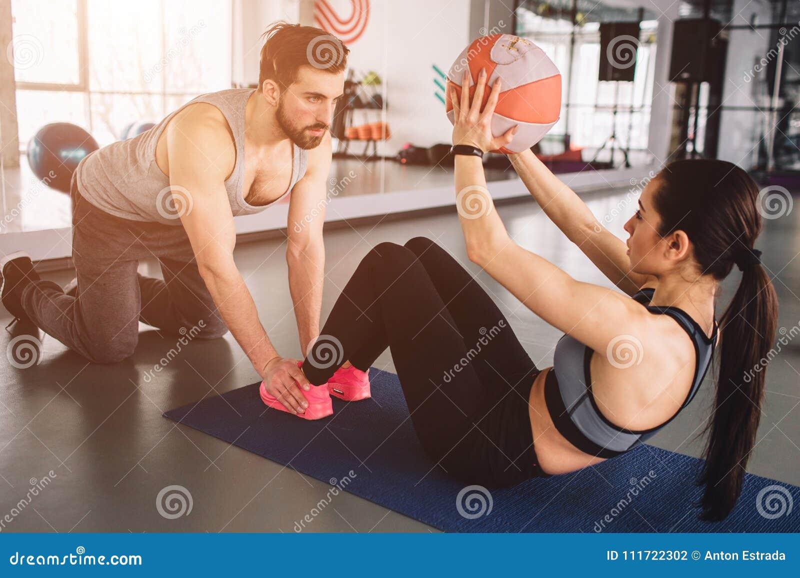 Een beeld die van meisje sommige abs doen oefent met de bal uit terwijl haar sportpartner haar benen op de vloer in bedwang houdt