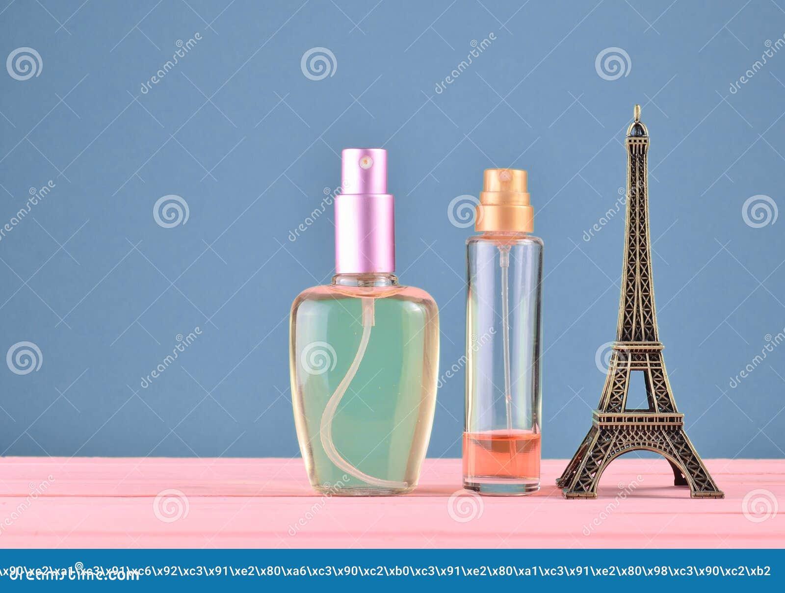 Een beeldje van de Toren van Eiffel, flessen parfum op een blauwe pastelkleurachtergrond, minimalistische tendens, ruimte voor te