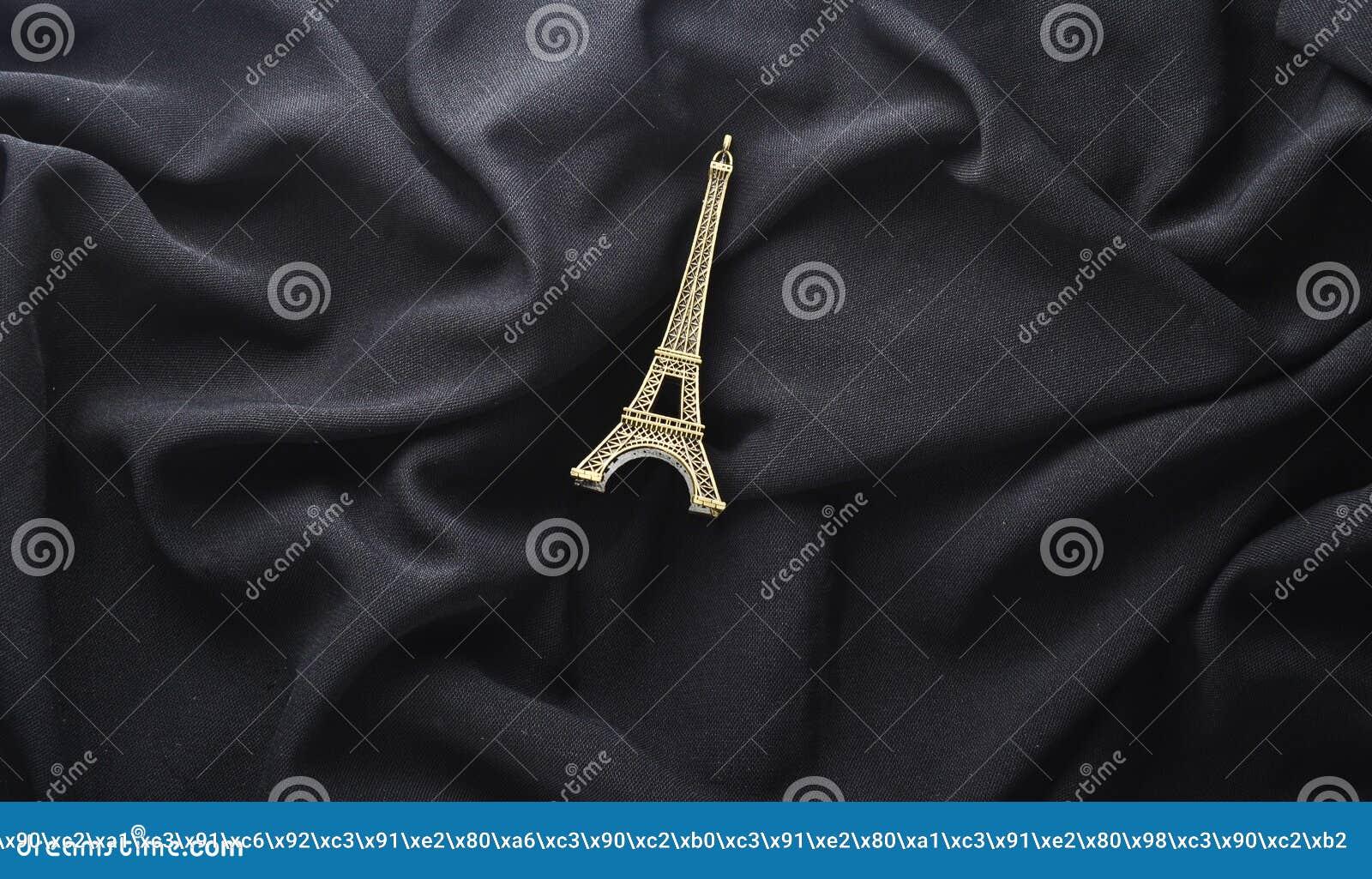 Een beeldje van de Toren van Eiffel op een zwarte stoffenachtergrond