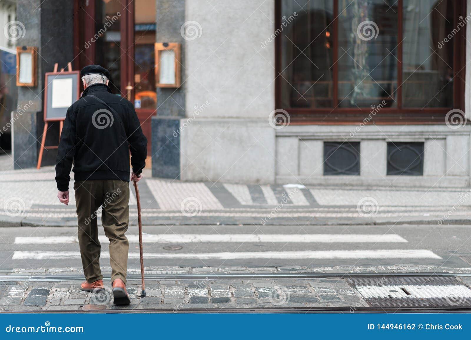 Een bejaard mannetje met een wandelstok loopt langzaam over een zebrapad in het midden van een alleen stad
