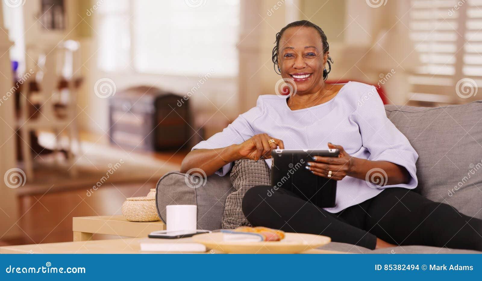 Een bejaard zwarte gebruikt gelukkig haar tablet terwijl het bekijken de camera