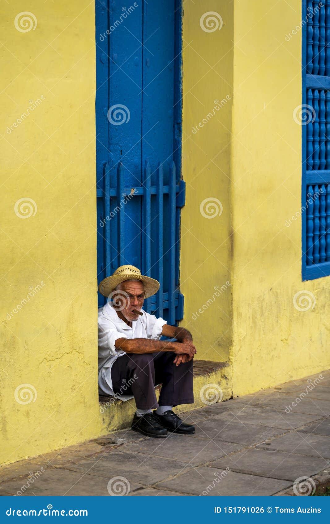 Een bejaarde Cubaanse zitting op een drempel, die een sigaar roken