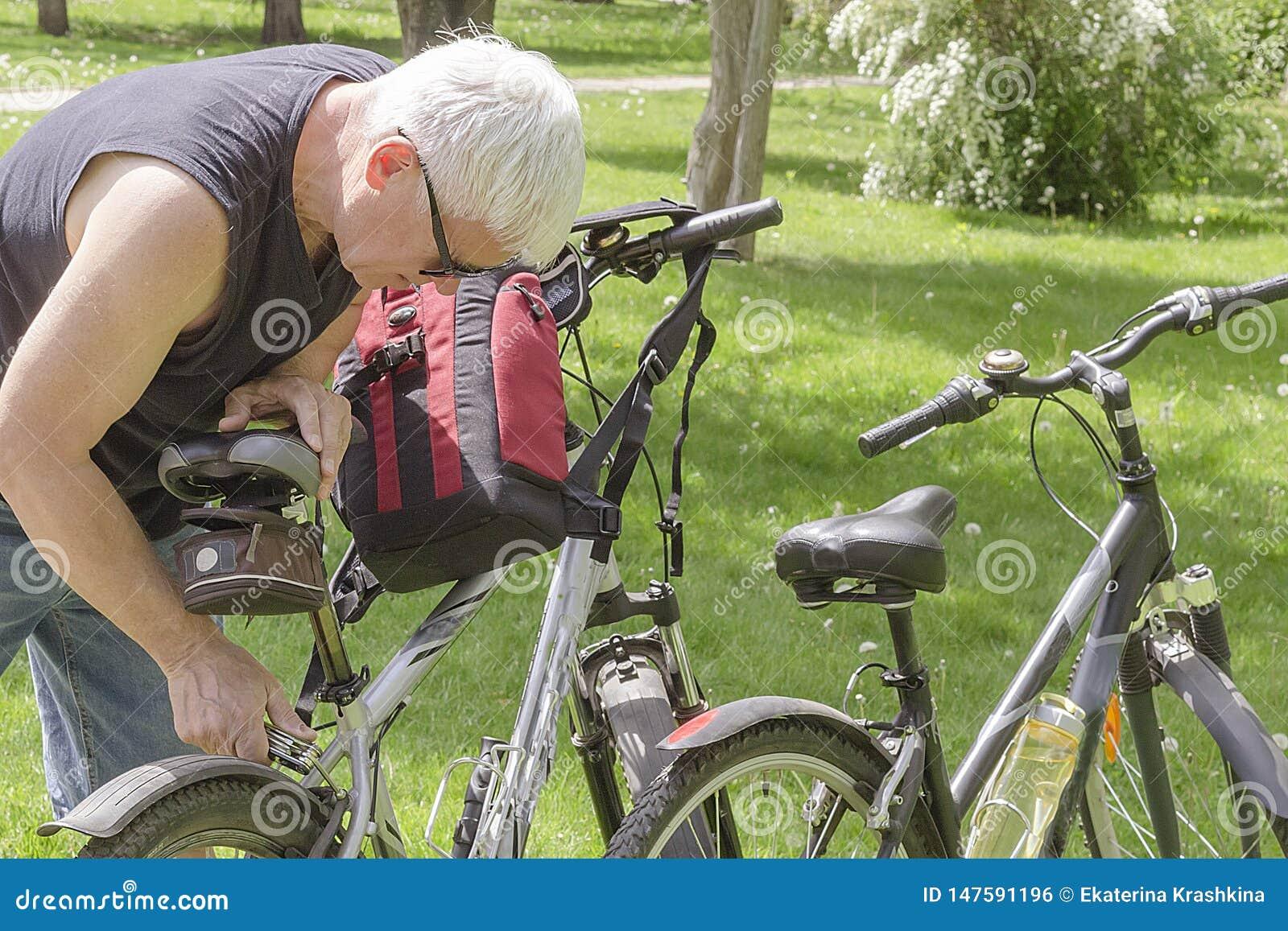 Een bejaarde die in zonnebril een fiets in het Park herstellen