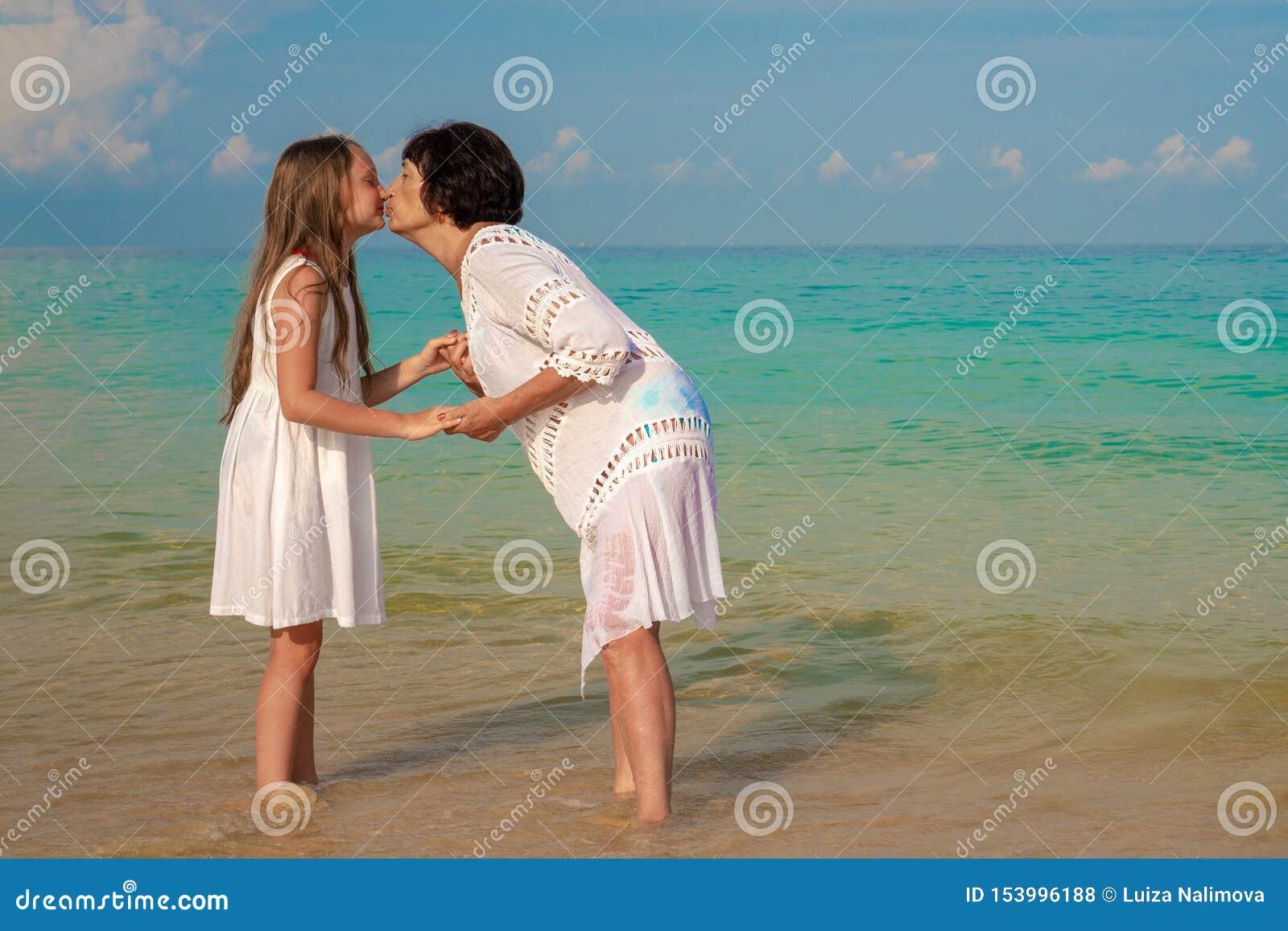 Een bejaarde en een mooi meisje op het strand De grootmoeder kust haar kleindochter op een zonnige dag Concept liefde en familie