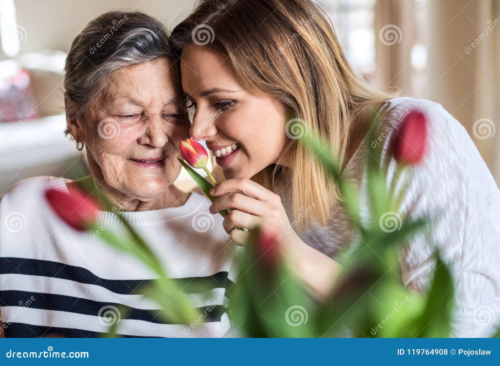 Een bejaarde grootmoeder met een volwassen kleindochter thuis, het ruiken bloeit