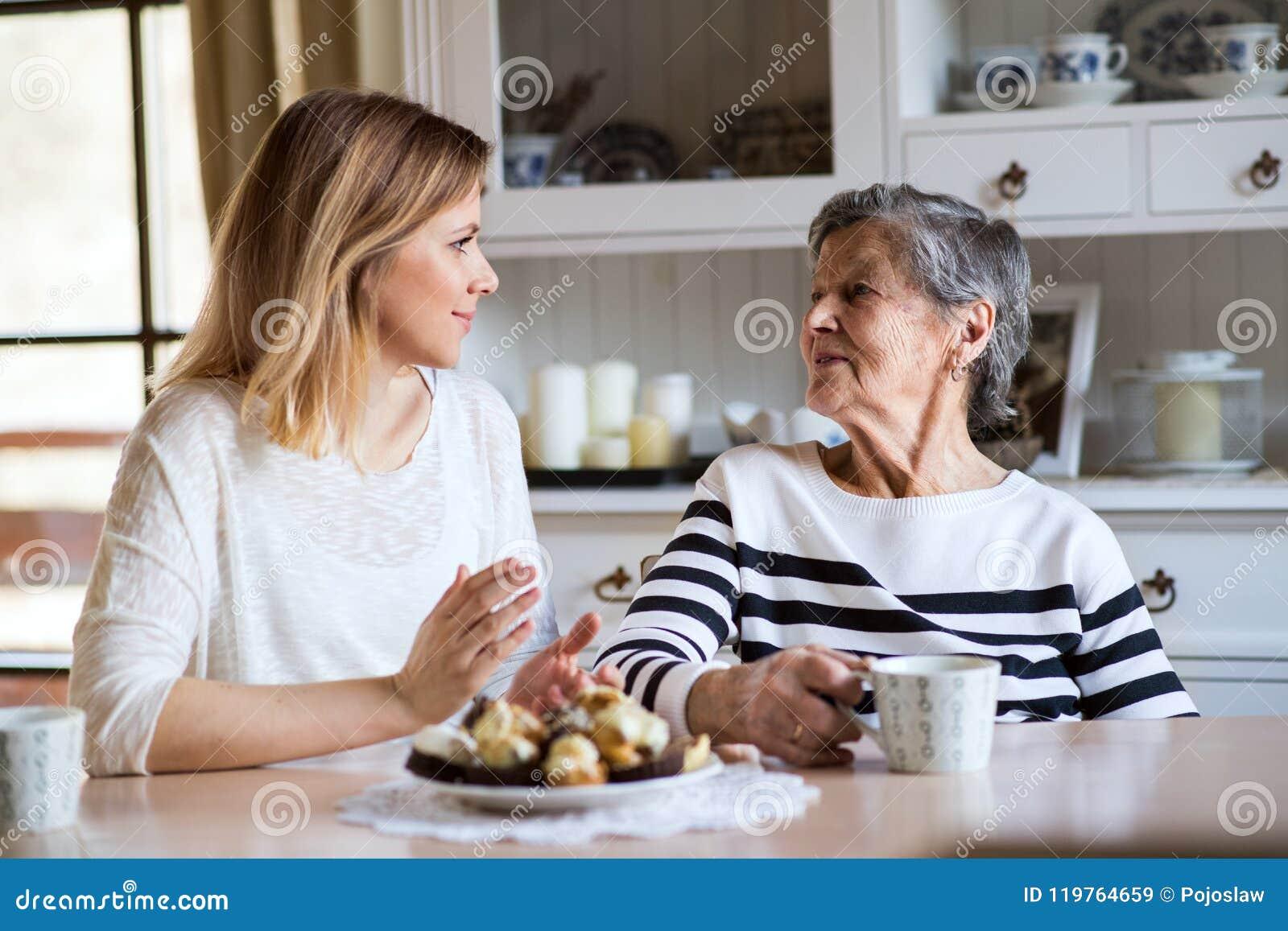 Een bejaarde grootmoeder met een volwassen kleindochterzitting bij de lijst die thuis, cakes eten