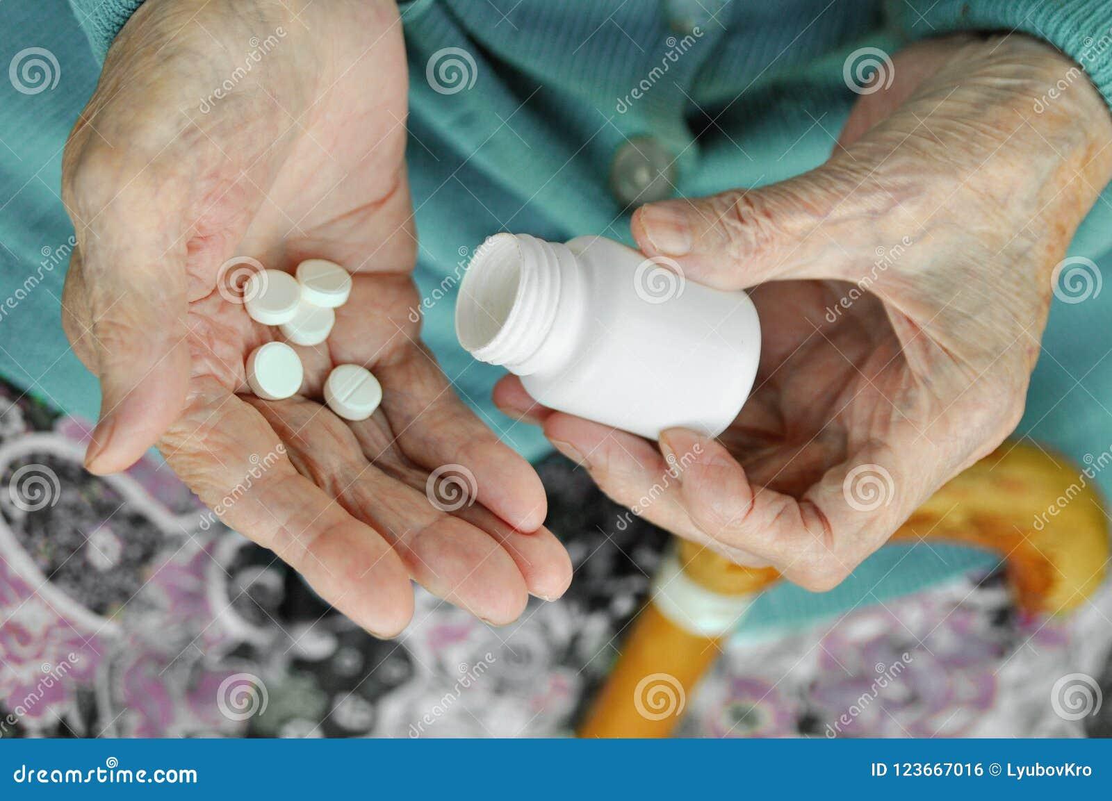 Een bejaarde met een riet die een pil en een container op de straat houden gezondheid Model Sluit omhoog