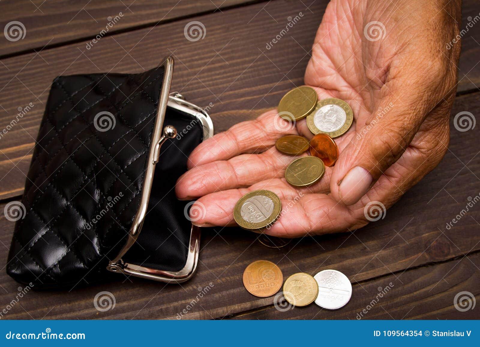 Een bejaarde persoon houdt de muntstukken over de oude lege portefeuille Het concept armoede in pensionering