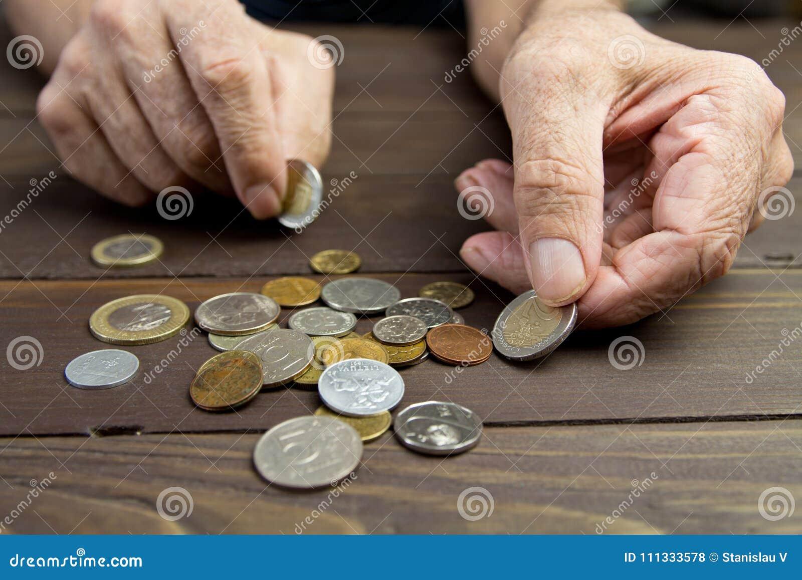 Een bejaarde persoon houdt muntstukken Handen van bedelaar met weinig muntstukken Het concept armoede