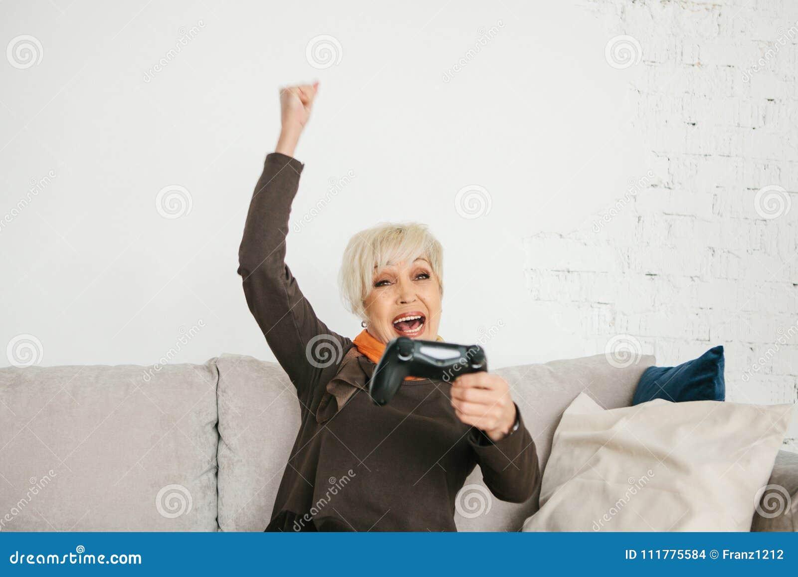 Een bejaarde speelt een videospelletje en gebaren dat zij won Bejaarde persoon en moderne technologie