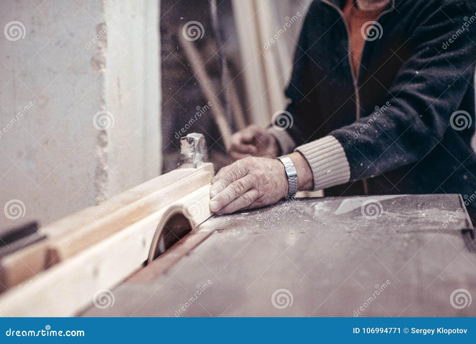 Een bejaarde timmerman zaagt een houten werkstuk