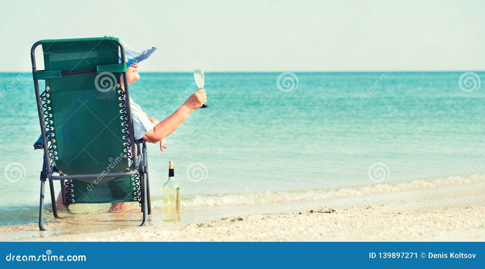 Een bejaarde zit op het strand op een chaise-longue en het drinken wijn