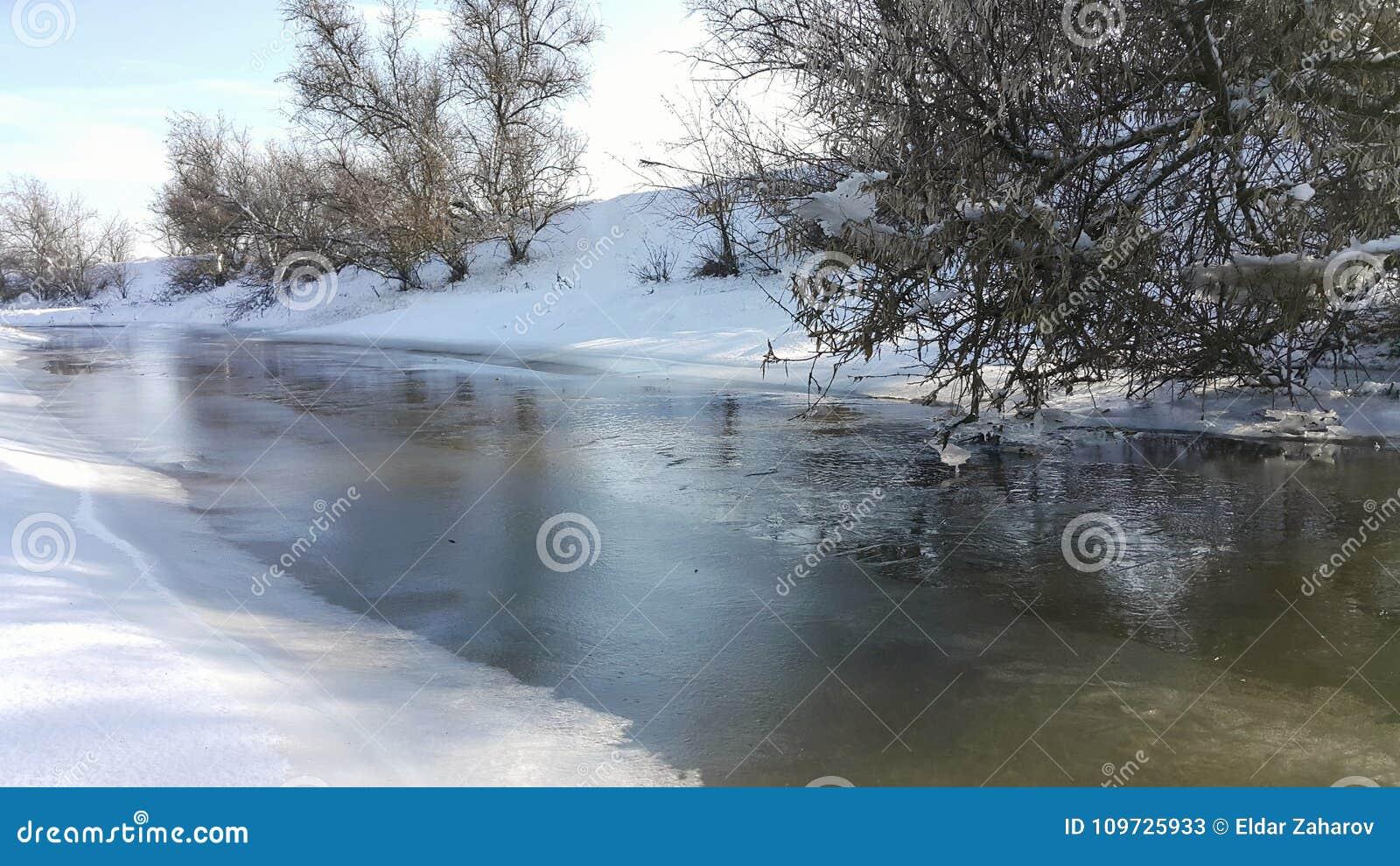 Een bevroren rivier in gevangenschap dichtbij de koude Sneeuw en blauwe hemel met wolken en stok Ik houd van op een bevroren rivi