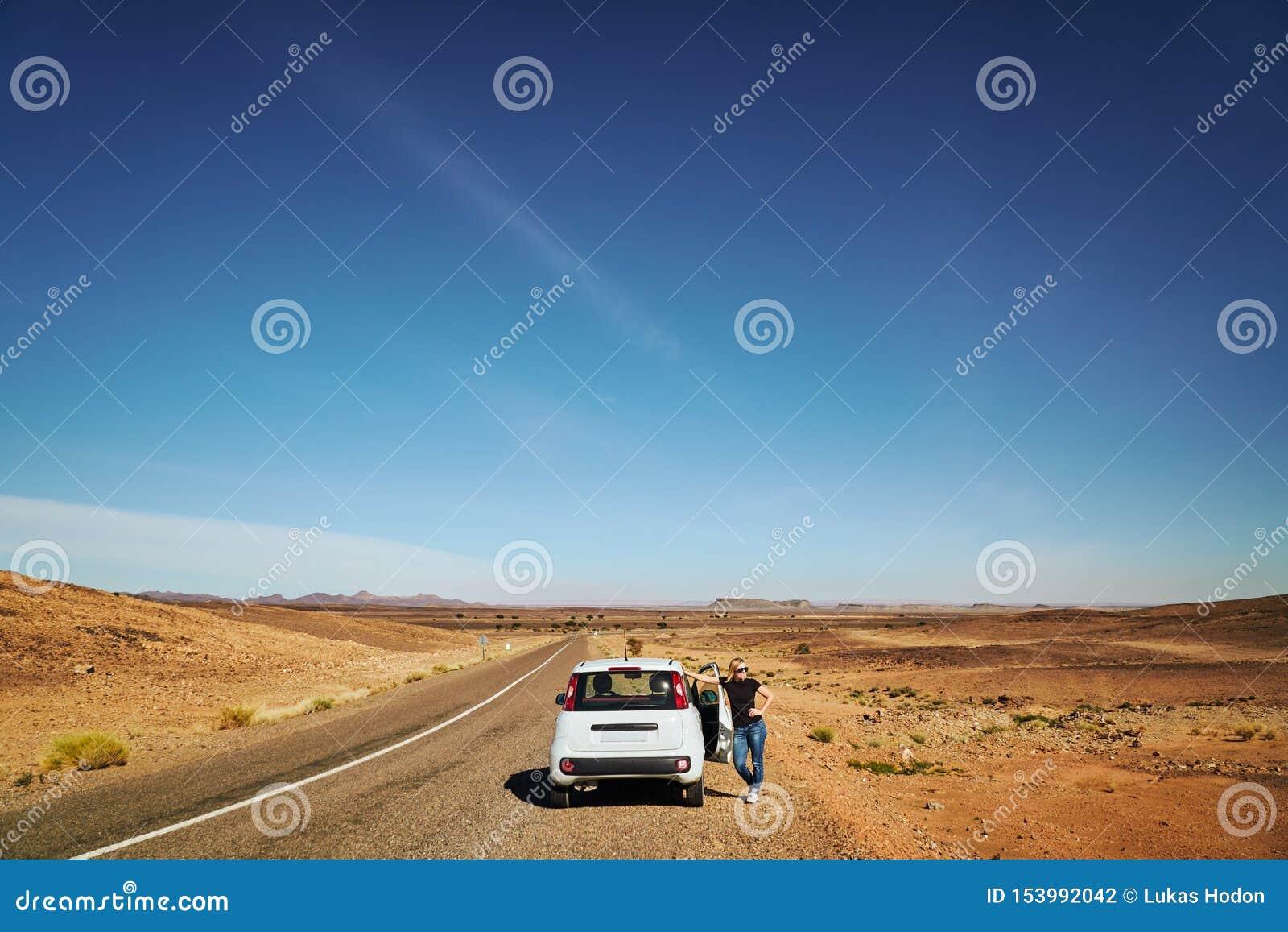 Een blondemeisje die zich in de woestijn naast de gebroken auto bevinden