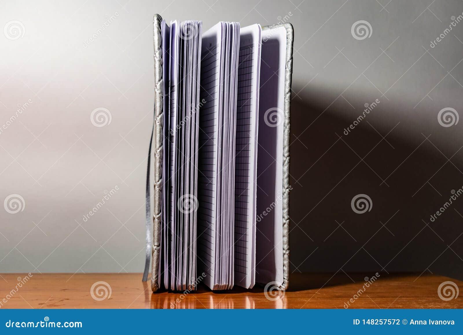 Een boek, een notitieboekje met een geruit patroon op een houten lijst in verschillend stelt De dekking is grijs en zacht met tex