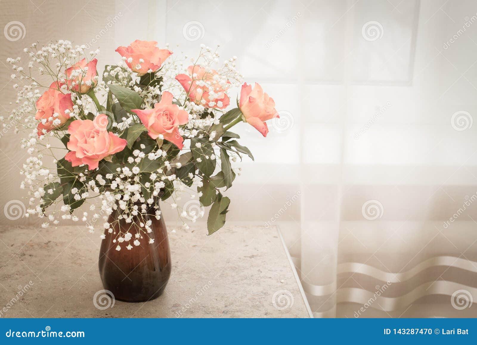 Een boeket van gevoelige rozen bevindt zich in een kleivaas op de lijst