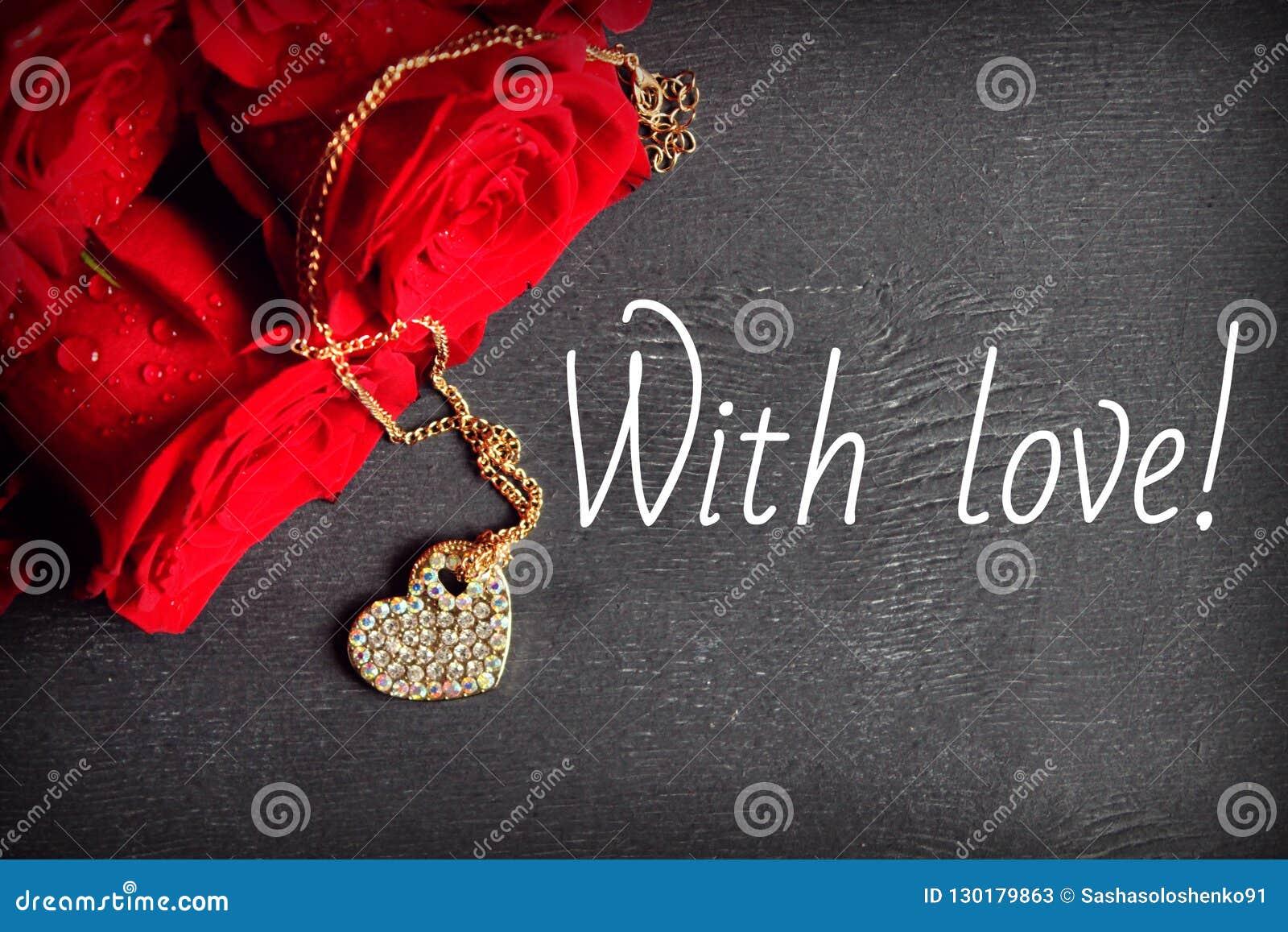 Een boeket van rode rozen en een gouden medaillon in de vorm van een hart op een houten zwarte achtergrond