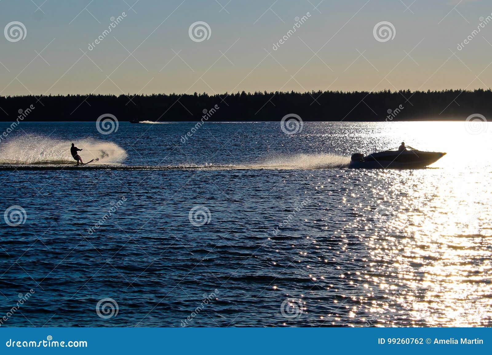 Een boot en waterskiër tegen een blauw meer wordt gesilhouetteerd dat