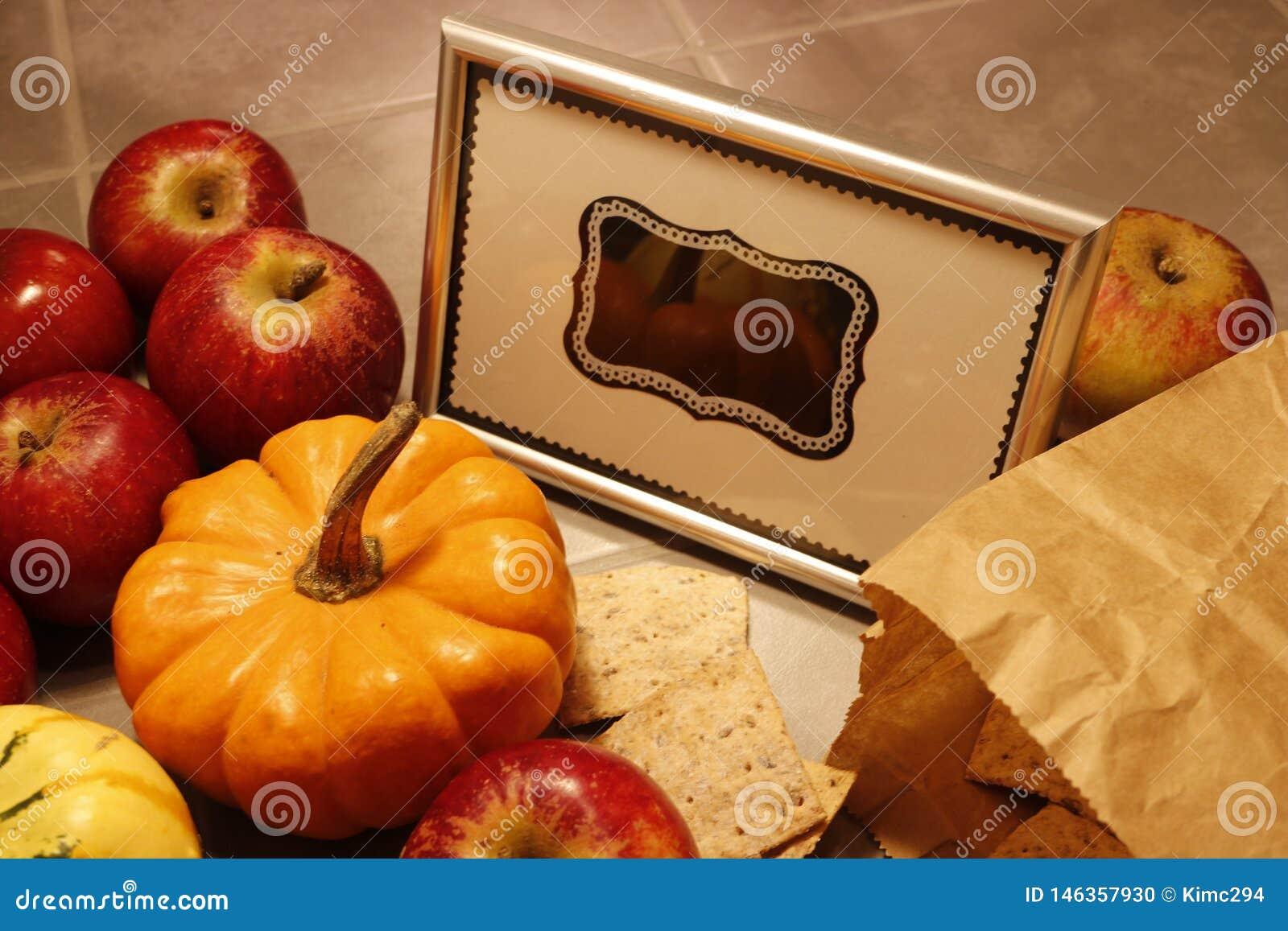 Een bos van rode appelen ligt naast het miniatuur pumpking Een ontworpen leeg bordteken bevindt zich in het midden