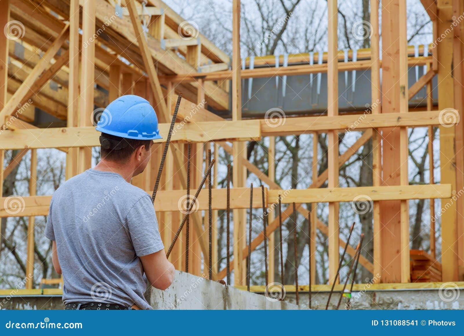 Een bouwinspecteur onderzoekt een nieuw huis inbouwt bouwwerf controlerend de nieuwe wordt uitgevoerd bouw